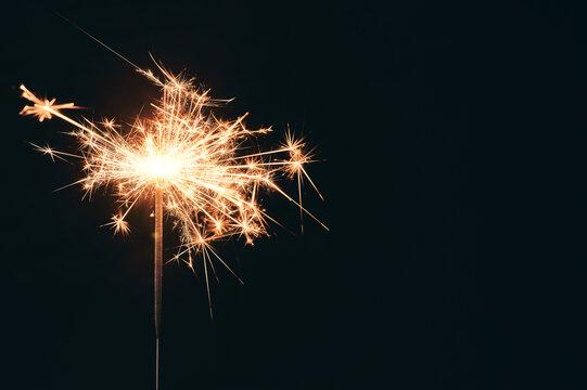 Burning party sparkler isolated on black background. Bengal