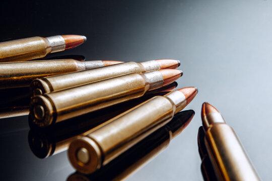 Rifle bullets or cartridges on black shiny background