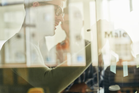 Abstract photo of smiley gentleman behind a glass window