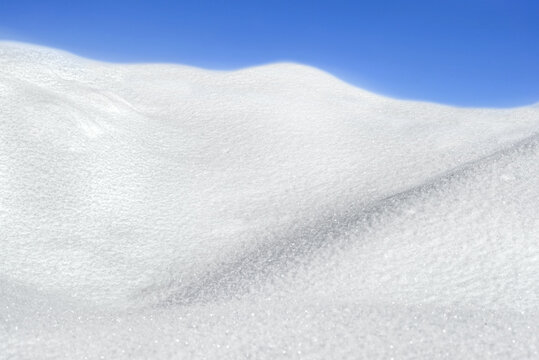 Snow texture or winter white background with wave and blue sky