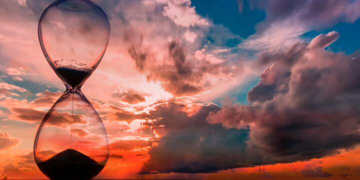 Time passing at sunset with hourglass
