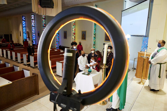 Service is live streamed using a ring light as Kayden Onyembi, 4 months, is baptized at Saints Peter and Paul Catholic Church in Atlanta