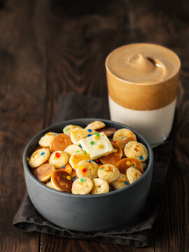 Mini pancakes cereal and dalgona coffee on brown wooden background, copy space. Trendy food and drink - tiny panckakes served sprinkles and whipped instant coffee with milk or dalgona coffee. Vertical