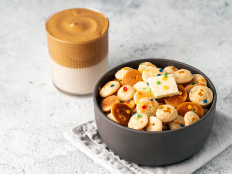 Mini pancakes cereal and dalgona coffee on gray cement background, copy space. Trendy food and drink - tiny panckakes served sprinkles and whipped instant coffee with milk or korean dalgona coffee