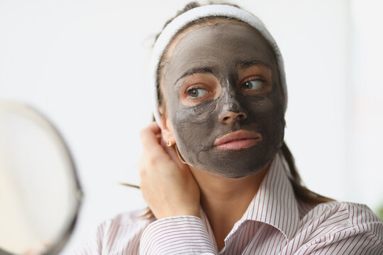 Young woman makes rejuvenating clay face mask. Facial skin care concept
