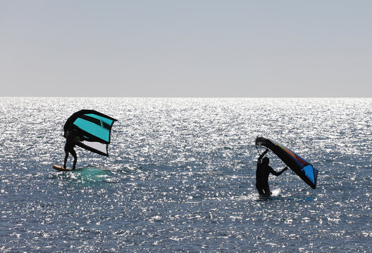 men practicing with wing-surfer at sunset in the sea