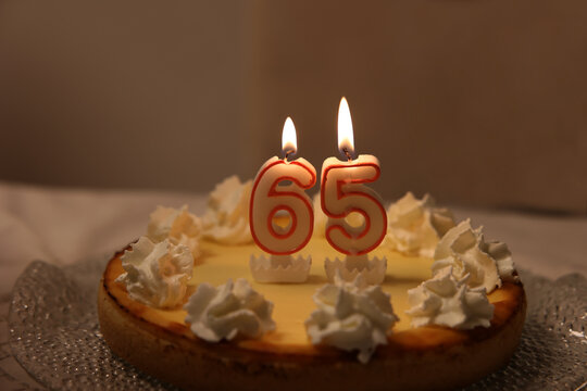 Closeup of a birthday cake with 65 candles on it on the table