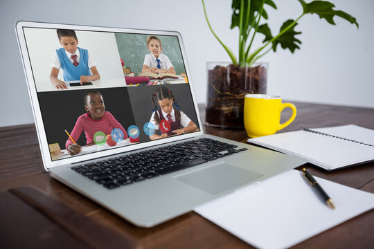 Webcam view of multiple students on video call on laptop on wooden table