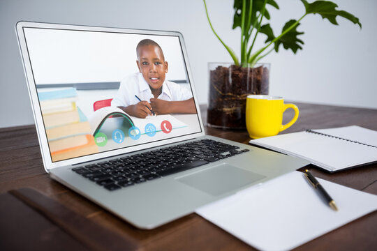 Webcam view of african american male student on video call on laptop on wooden table