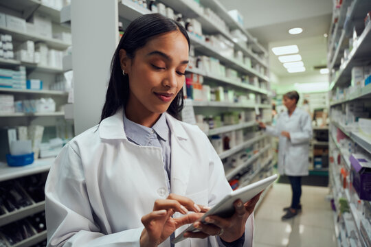 Smiling young female worker in pharmacy wearing labcoat checking inventory using digital tablet
