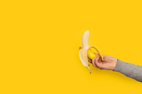 Mano femenina sosteniendo un plátano fruta sobre un fondo amarillo liso y aislado. Vista de frente. Copy space. Concepto de nutrición, salud.