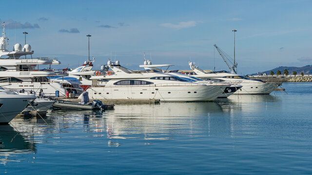 Ships, yachts and boats on blue surface of Black Sea by pier of Commercial seaport of Sochi. Resort city center. Sochi, Russia - November 23, 2020