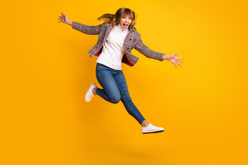 Wall Mural - Full size portrait of excited pretty girl jumping raise hands open mouth isolated on yellow color background