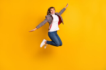 Wall Mural - Full size photo of pretty cheerful girl raise arms flying beaming smile look camera isolated on yellow color background