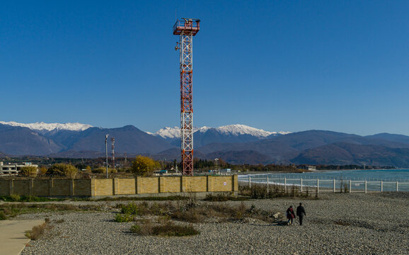 View of border with Abkhazia from Russia side in Sirius village. High tower with radar against Caucasus mountains with snowy peaks. Sunny winter day. Sochi, Russia - December 08, 2020