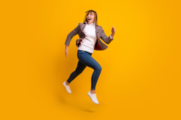 Wall Mural - Full size profile photo of impressed young girl open mouth look interested empty space isolated on yellow color background