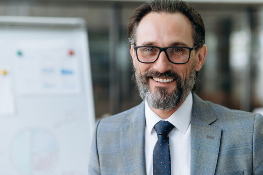 Close-up portrait of mature bearded businessman dressed in stylish suit and eyeglasses, looking at the camera with friendly smiling, standing in the office