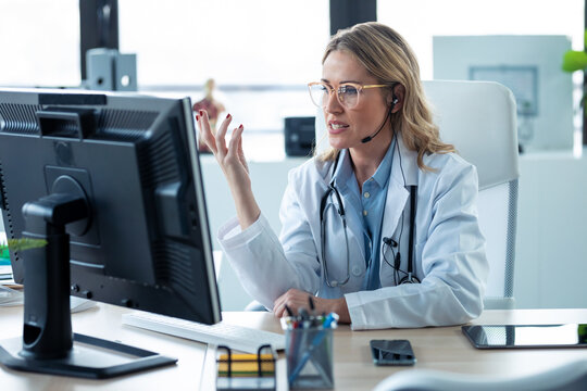 Mature attractive female doctor talking while explaining medical treatment to patient through a video call with computer in the consultation.