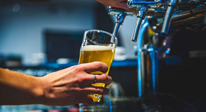 bartender hand at beer tap pouring a draught beer in glass serving in a restaurant or pub