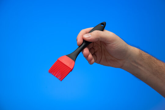 Caucasian male hand holding silicon red and black kitchen brush isolated on blue background