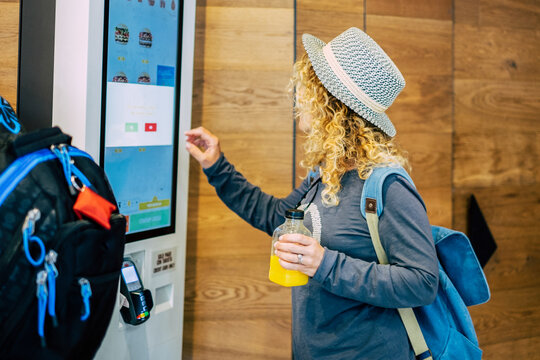 Woman make food order in modern display at fast food restaurant - self-service panel technology and people in travel lifestyle taking hamburger to eat