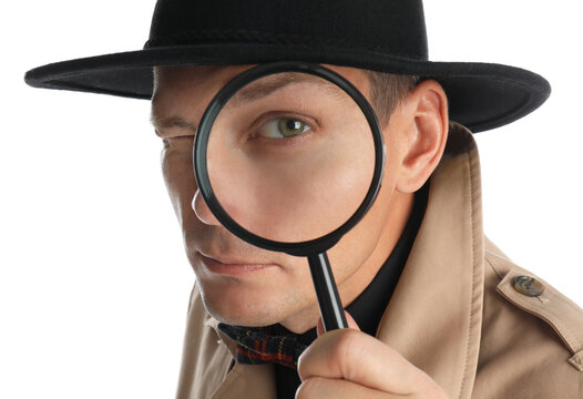 Male detective looking through magnifying glass on white background