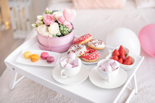 Flowers and sweets on white table and balloons on the white bed. Gift for Valentine's day or March 8 or Mother's Day or birthday