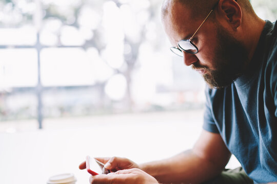 Serious man touching screen of smartphone
