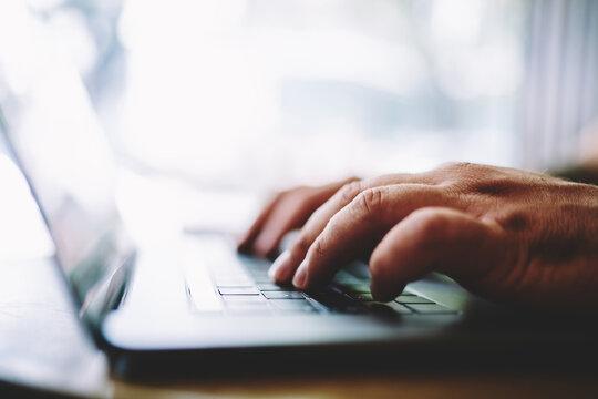 Man typing message on laptop during work