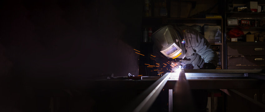 An adult male works in an old workshop. He holds a welding machine in his hand and welds the metal structure. Copy space.