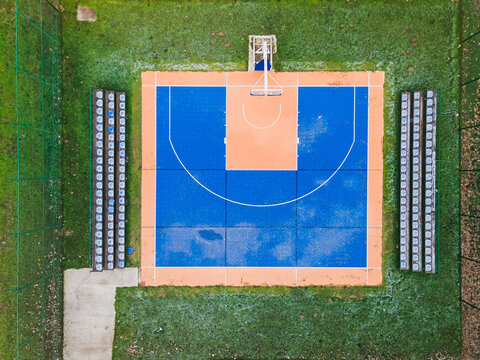 Colorful basketball  field from above. Outdoor sports ground with blue and orange surface for playing basketball,  lamps and benches for spectators