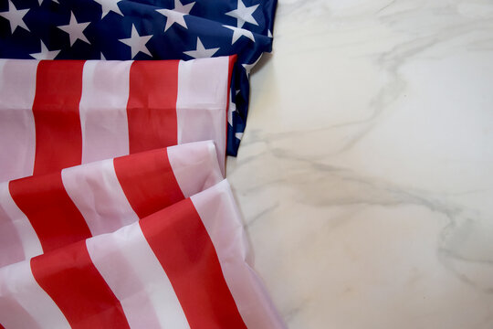USA flag on marble background, top view, place for your text. American flag lying on a marble slab. Place for your inscriptions. National holiday concept