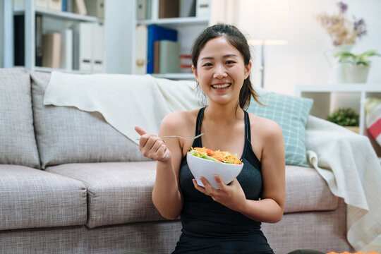 young asian elegant woman eating bowl of healthy salad after working out at home. happy girl face camera smiling while enjoy meal sitting on floor by sofa in home living room. hungry sporty girl.