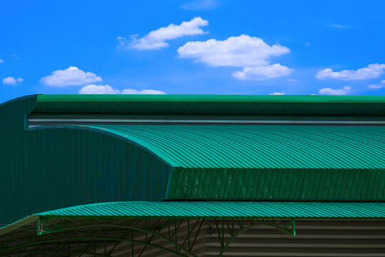 Green metal curved roof of warehouse building against blue sky background