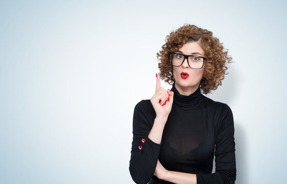 Young beautiful woman wearing glasses and casual black turtleneck over blue isolated background pointing finger up with successful idea.