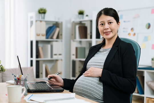 Portrait of elegant asian korean pregnant business woman in suit using laptop computer in modern office. beautiful maternity lady worker face camera smiling. confident female worker with big belly