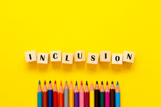 Inclusion concept word on wooden cubes and pencils on yellow background