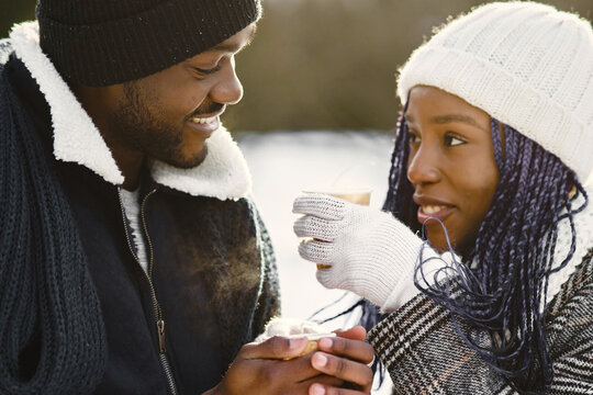 People walks outside. Winter day. African couple with coffee.