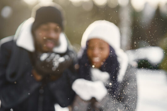People walks outside. Winter day. African couple
