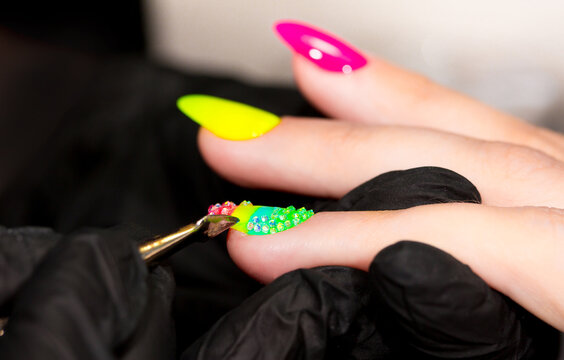 Manicure rainbow neon colors with pasted diamond rhinestones. Manicurist paints nails client. Neon colors on the nails. Beauty salon, beauty treatments.