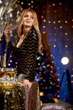 beautiful blonde woman in sequins party dress holding festive balloons in luxury interior. party and holiday celebration