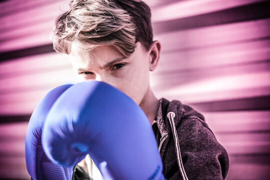 Portrait of handsome young male with boxing gloves ahead the face. Boy ready for a boxe workout defending the head with hands. Boxer ready to throw punches. Sport determination and competition concept