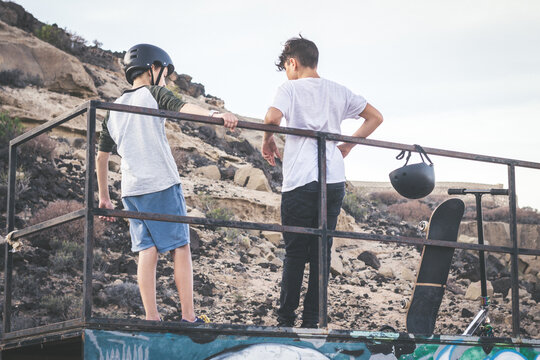Trendy teenagers enjoying free time at the skate park, standing on half pipe ramp. Two young boys talking about tricks and jumps after a day at the skatepark. Youth togetherness and friendship concept
