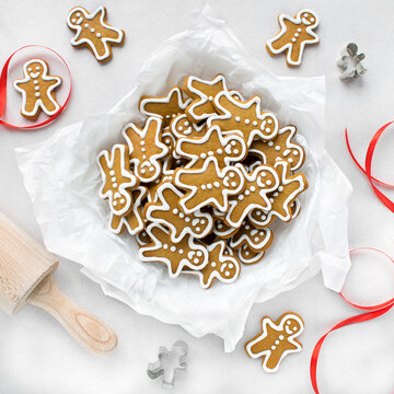 Gingerbread men on a white tablecloth next to a red ribbon and cookie cutters.
