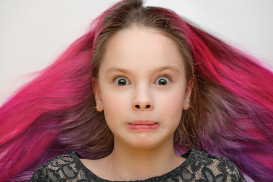 a child with dyed hair and a surprised expression