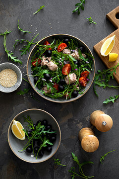 Fresh vegetable salad with tuna, arugula, olives and tomatoes. Healthy food concept, top down view