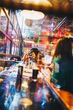 A man standing at a bar looking at the menu