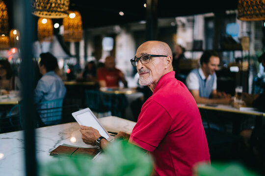 Contemplative male blogger in optical eyewear thoughtful looking away during leisure time in coffee shop, Caucasian man with modern digital tablet resting in public cafe with good internet connection