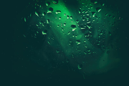 Abstract dark green background with raindrops on wet glass, water drops. Blurred style, selective focus
