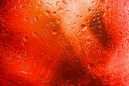 Abstract red background with blurred raindrops on glass, illuminated neon lights. Modern background